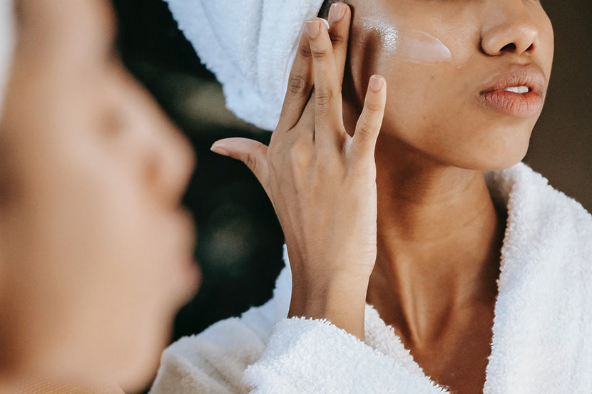 A woman with glowing skin applying brightening product like vitamin C serum by SLMD Skincare