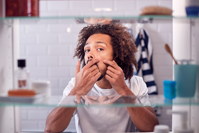 A man poking at a pimple that needs Spot Check salicylic acid acne patches by SLMD Skincare