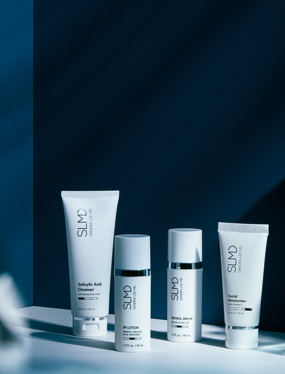 A blue hued photograph of the 60 day kit SLMD Acne System: Salicylic Acid Cleanser, BP Lotion, Retinol Serum, Facial Moisturizer