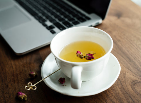 cup of white tea on a brown desk