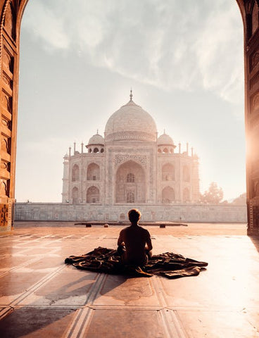 man sitting down at a grandiose temple