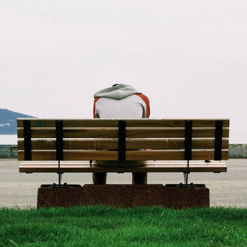 man sitting on bench with his head down