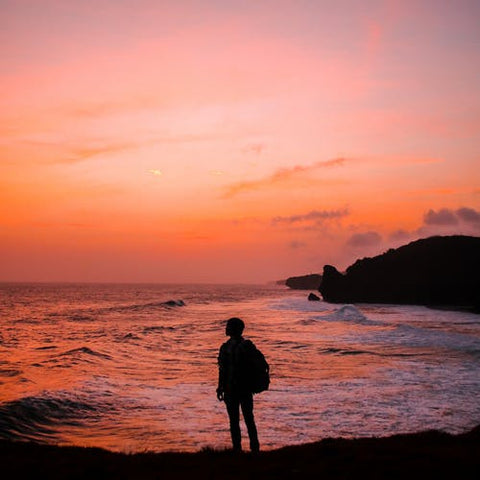 silhouette of man with backpack staring off into the ocean sunset