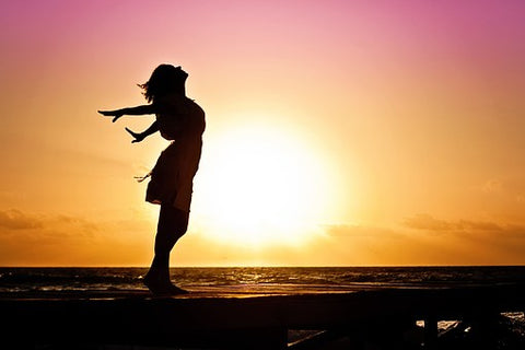 woman with arms stretched behind her in front of the sunset