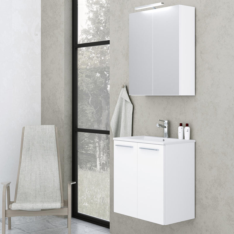 Bathroom Mirror Cabinet with Light and Shaver Plug White installed on a bathroom wall and matching bathroom vanity unit and chair