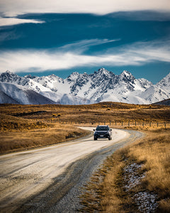 Car-Driving-Down-Road-Mountains-Grass-Hakatere-Canterbury-New-Zealand-Mark-Hannah-Photography