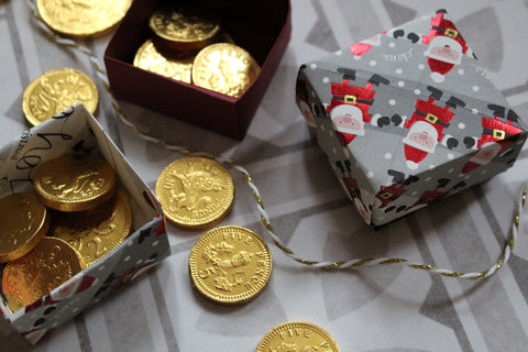 Photograph showing origami boxes made with Christmas wrapping paper and filled with chocolate coins