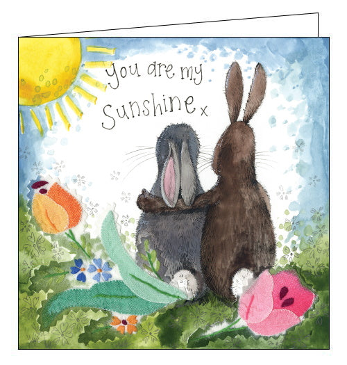 Part of Alex Clark's Sunshine card collection, finished with gold foil. This lovely greetings card shows two rabbits sitting together in a garden, looking towards the sun. Gold text on the front of the card reads