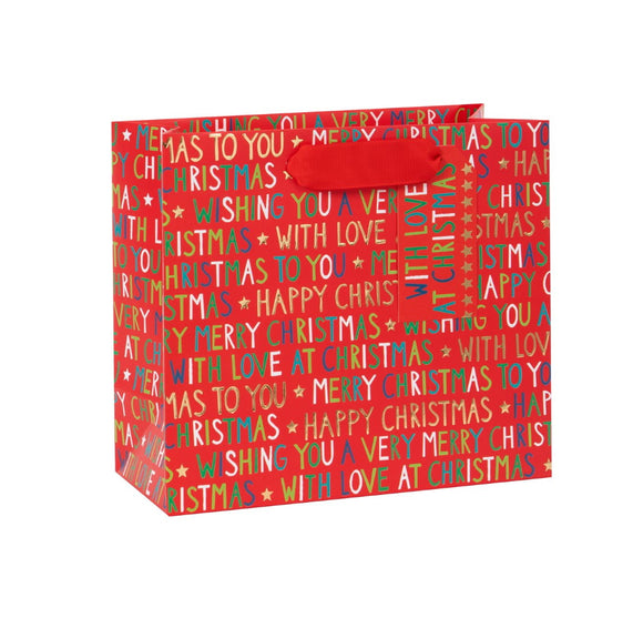 This Christmas gift bag is decorated with a repeating pattern of green, white and gold text of Christmas greetings such as