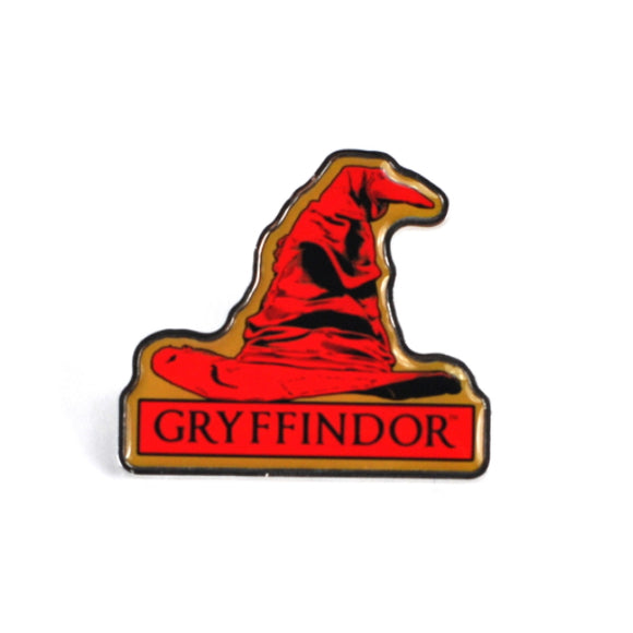 This enamel pin badge is shaped like the famous Hogwarts Sorting Hat, but coloured red to signify the chosen house. Below the sorting hat black text reads