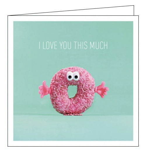 This Valentines card features a pink sprinkle dougnut with plastic hands and plastic eyes. Text on the front of the card reads