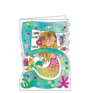 This lovely little 5th birthday card is decorated with a blonde mermaid, whose rainbow-coloured tail is embellished with silver scales, and her fish friends playing around a large green number 5.