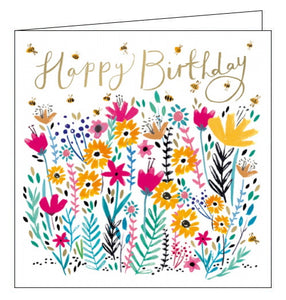 "This charming birthday card is decorated with a field of brightly coloured wildflowers being visited by tiny bubble bees. Gold text on the front of the card reads ""Happy Birthday""."