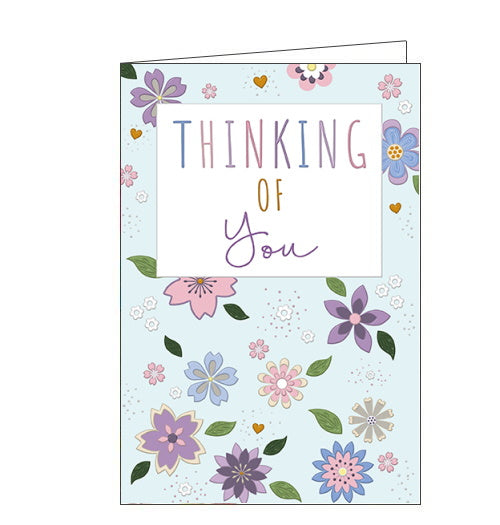 This thinking of you card is decorated with a scattering of pink and purple flowers, interspersed with tiny gold hearts, against a pale blue background. Text on the front of the card reads