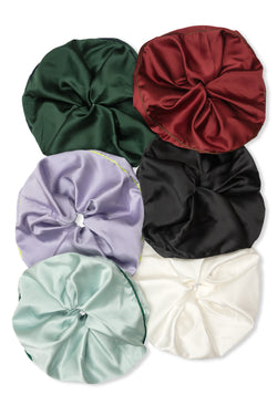 Shayne jumbo scrunchies available for purchase as a set of six. This includes six oversized silk hair ties in olive green, black, red, mint, white, and purple.