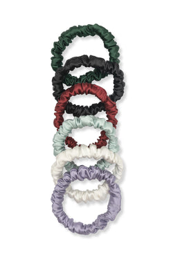 Shayne mini scrunchies available for purchase as a set of six. This includes six skinny silk hair tie replacements in olive, black, red, mint, white, and purple.