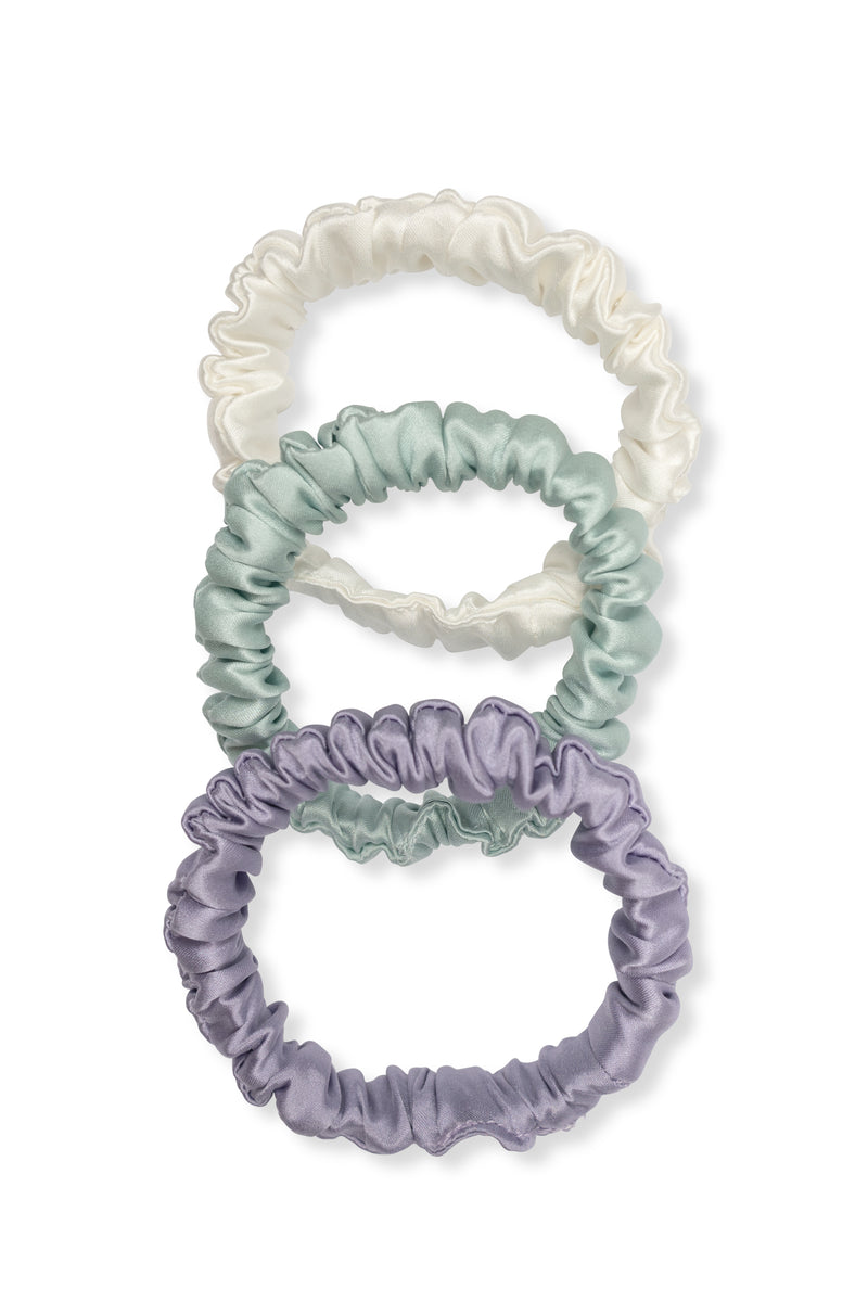 Shayne mini scrunchies available for purchase as a set of three. This set includes three silk hair ties in white, light blue mint, and purple.