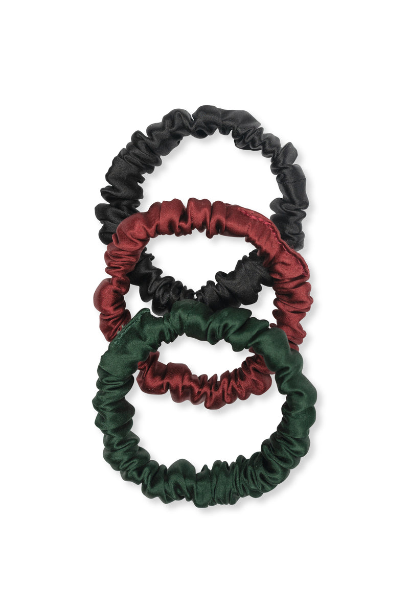 Shayne mini scrunchies available for purchase as a set of three. This set includes three silk hair ties in black, olive, and plum.