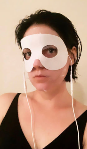 The Organic Esthetician using a sheet mask with conductive eye mask from 7e wellness