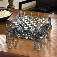 "BATTLEGROUND CHESS SET-The Decor Source-13½"" x 13½"" x 5⅜"" high; tallest piece is 3"" high; smallest piece is 2⅜"" high.-Polyresin and glass.-The Decor Source"