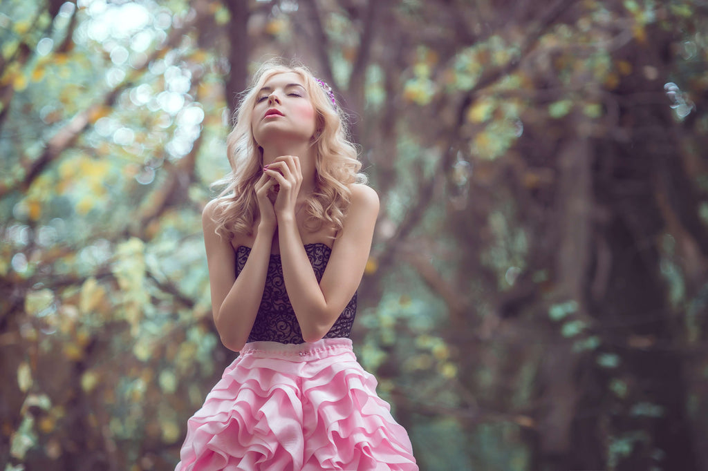 Young woman in a forest clasping hands and looking up, wearing a pink ruffle skirt