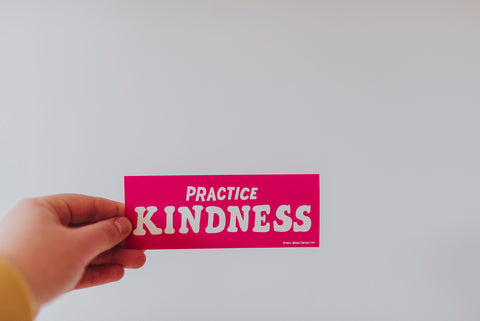 Practice Kindness sticker against a wall