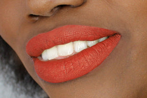 orange red lipstick shade on dark skin model