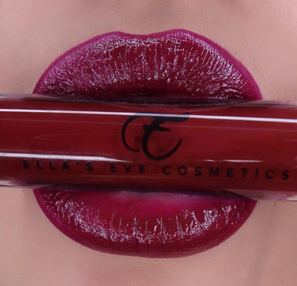 image of wine berry lips holding lip gloss bottle in wine berry shade