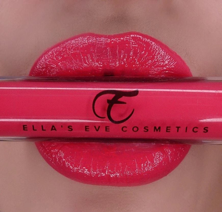 image of coral lips holding lip gloss bottle of coral shade
