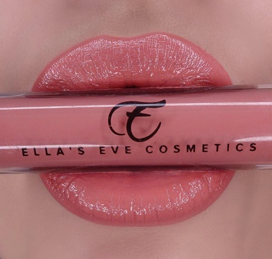 image of peach nude lips holding lip gloss bottle in peach nude shade