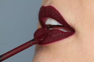 light skin model's lips with mid tone wine berry shade matte lipstick