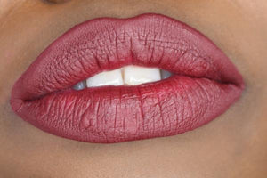 deep skin model's lips with mid tone wine berry shade matte lipstick