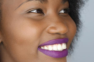 dark skin model wearing plumish purple lipstick shade