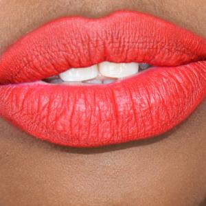 dark skin model's lips in classic cherry red shade lipstick