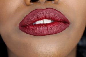 dark skin model's lips with ruby red lipstick shade