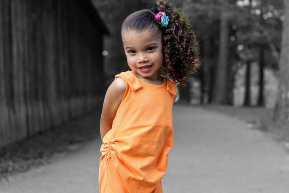 Afro Colombian child outside standing with hand behind their back, smiling. Tight Curly hair in high side pony tail, blue and pink flowers at base of pony tail.  Child is wearing an orange tank style romper With hidden torso adjusters and shoulder snaps.