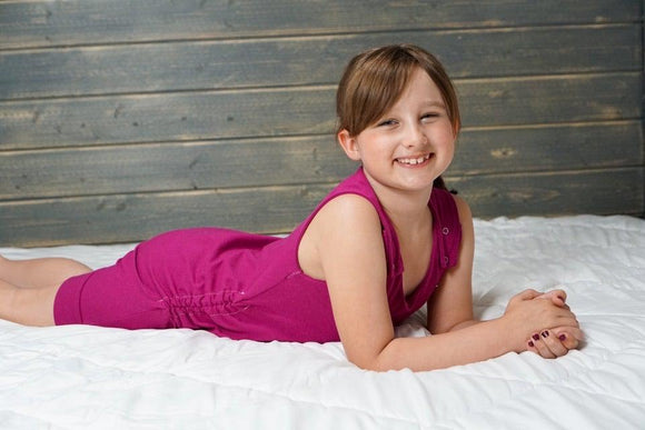 Brunette Caucasian child laying on their stomach on a white blanket, wooden slat background, hands cupped together and smiling wearing bright merlot tank style knee length romper with hidden torso adjusters and shoulder snaps