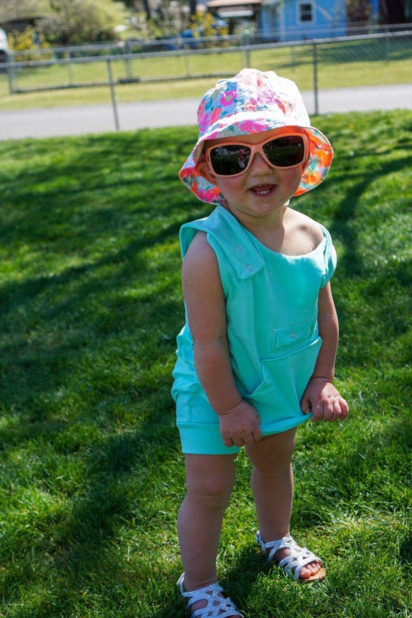 Caucasian toddler standing outside in the grass smiling, hands on stomach. Wearing brightly colored floral sunhat, peach sunglasses with black lenses and tank style thigh  length romper with hidden torso adjusters and shoulder snaps, medi pocket with snap, kangaroo pocket and inseam snaps