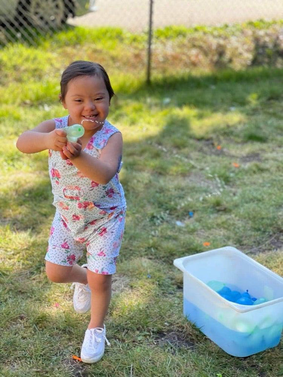 Brown haired child with Down syndrome standing on one foot outside in grass squeezing a green water balloon, some water shooting out, with a Clear rectangular container of green and blue water balloons sitting on the ground. Child wearing white shoes and a tank style romper with shoulder snaps, hidden torso adjusters, in seam snaps, kangaroo pocket and medi pocket with snap. Romper is a white background with Teal polka dots, orange and pink flowers with green leaves.