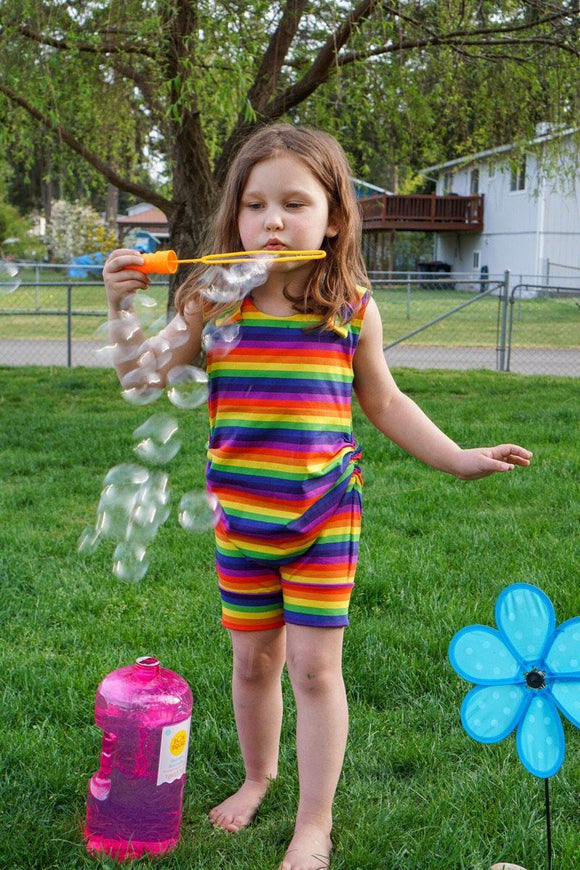 Brown haired Caucasian girl blowing bubbles outside in the grass in front of a tree wearing a rainbow stripe short length tank romper with hidden torso adjusters and shoulder snaps.