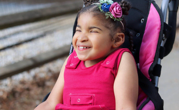 Afro Colombian child outside sitting in a medical stroller smiling with eyes closed, hair in two buns pink and floral headband. Wearing pink tank style romper with shoulder snaps, hidden torso adjusters, medi pocket with snap, kangaroo pocket below,