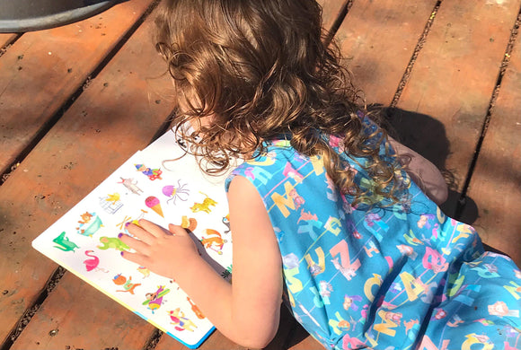 Curly Red haired Caucasian child laying on stomach wood slat deck looking at colorful alphabet book with white pages, wearing blue tank style romper with shoulder snaps and hidden torso adjusters featuring colorful letters and animals that start with the letter.