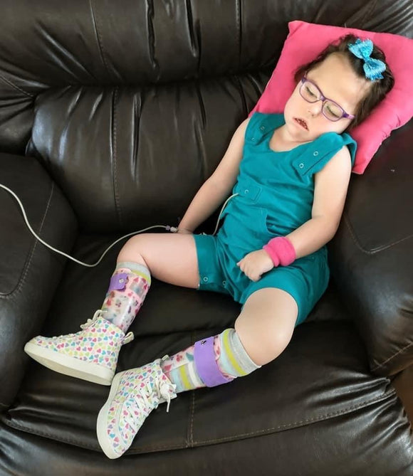 Dark haired Caucasian medically complex child with teal hair bow, purple eyeglasses and leg braces sitting on a black couch, head resting on pink pillow wearing teal tank style thigh length romper, with hidden torso adjusters, inseam snaps, shoulder snaps, kangaroo medi pocket with tube coming out. White high top tennis goes with colorful polka dots and pink arm band on left wrist