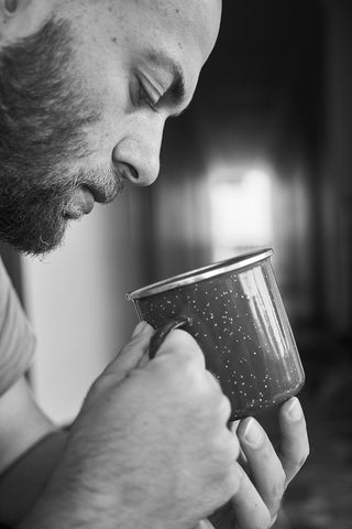 Man Examining Mug of Tea