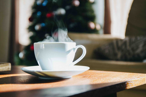 Tea cup in front of Christmas tree