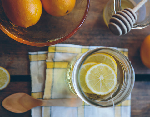 Lemon in a glass with bowl of citrus