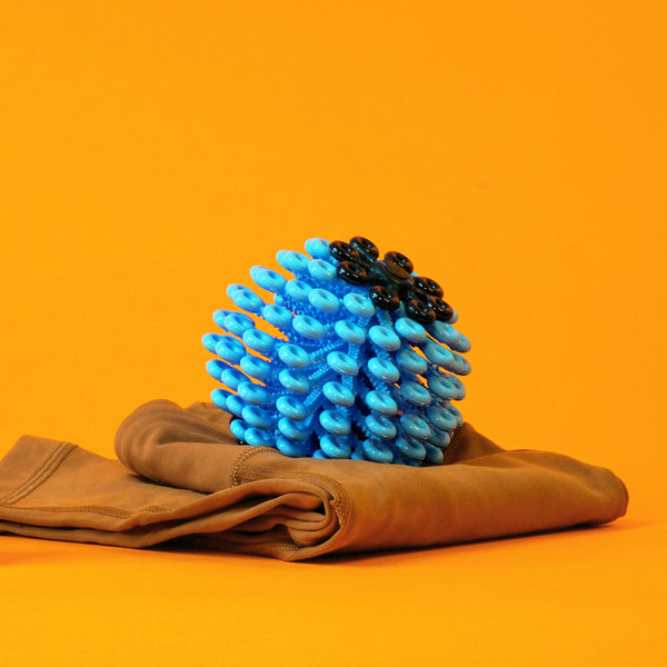 Placed atop a folded pair of leggings is an avant-garde laundry ball used to catch microfibers; the ball is blue with numerous loops, and the design is modeled after coral reef