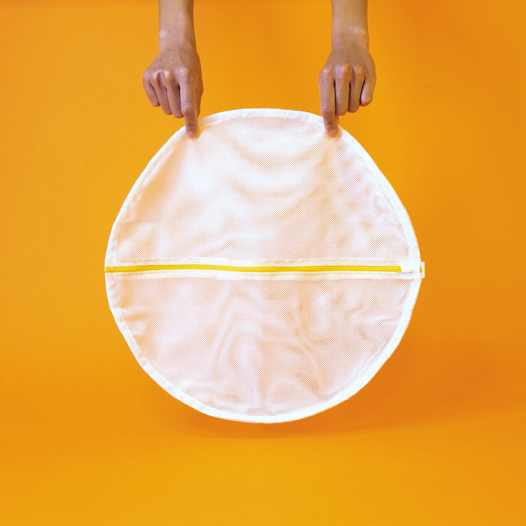 Mesh circular delicates bag by Soak held by two hands from above