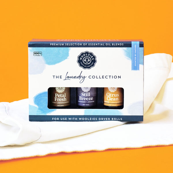 Woolzies laundry essential oil set of three small vials with purple and burnt orange labels inside white box with orange backdrop