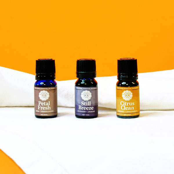 Woolzies laundry essential oil set of three small vials with purple and burnt orange labels shot on white fabric with orange backdrop